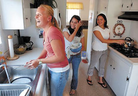 Becky Lane, left, a 27-year-old teacher at Santa Barbara High School, pitches in with some dishwashing as her roommates, 23-year-old Mary Derby, center, and 20-year-old Allison Low, look on.
