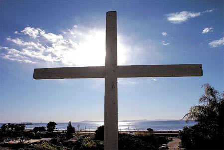 After the mudslide in 2005, shown below, some La Conchita residents built crosses in memory of the people killed, above. They covered the crosses in pieces of broken mirrors so that when the sun set over the ocean, they captured the fading light and reflected it outward.  MIKE ELIASON / NEWS-PRESS FILE